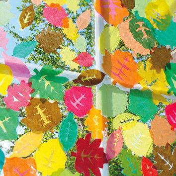 Wild durcheinander auf- bzw. nebeneinandergeklebtes Herbstlaub leuchtet am Fenster in warmen Herbsttönen